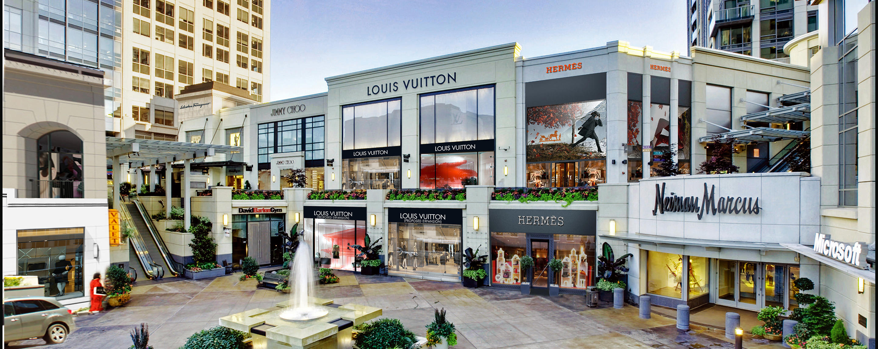 An open area in an outdoor shopping center is surrounded by stores such as Jimmy Choo, Louis Vuitton