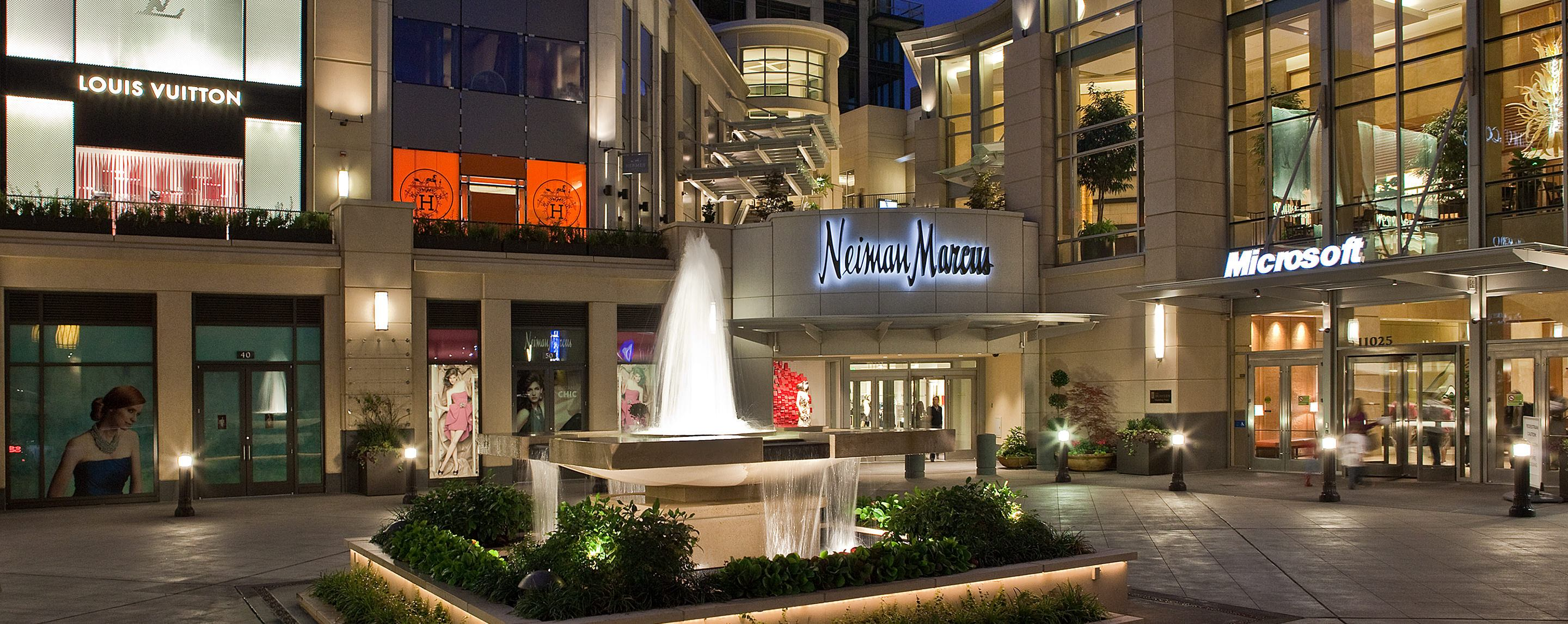 Louis Vuitton, Chic, Neiman Marcus, and Microsoft stores surround a fountain at an outdoor mall at dusk.