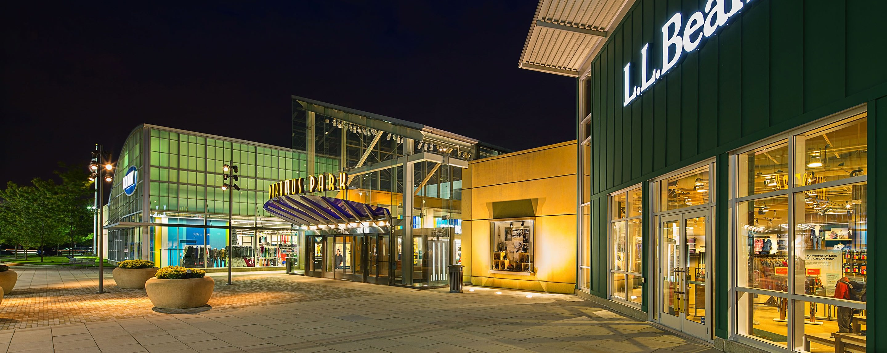 The sidewalks in front of the stores of Paramus Park appear to be empty at night time.