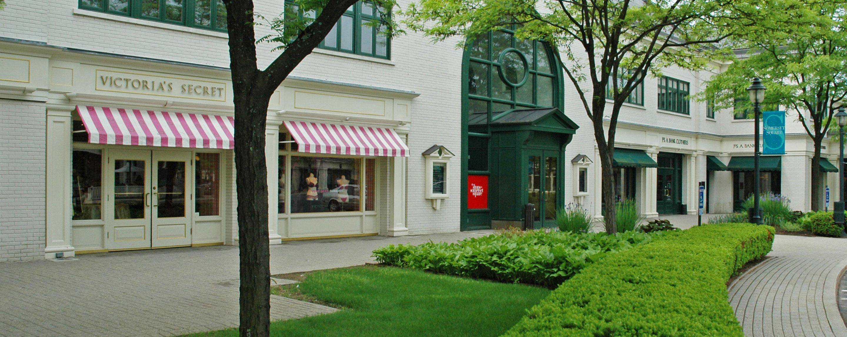 A Victoria's Secret storefront is stands behind a walkway and lush green landscaping.