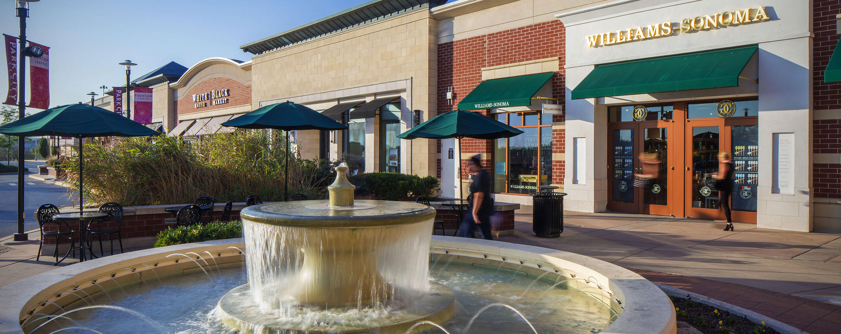 A man walks by a fountain outside of the Williams-Sonoma store in a outdoor shopping center.