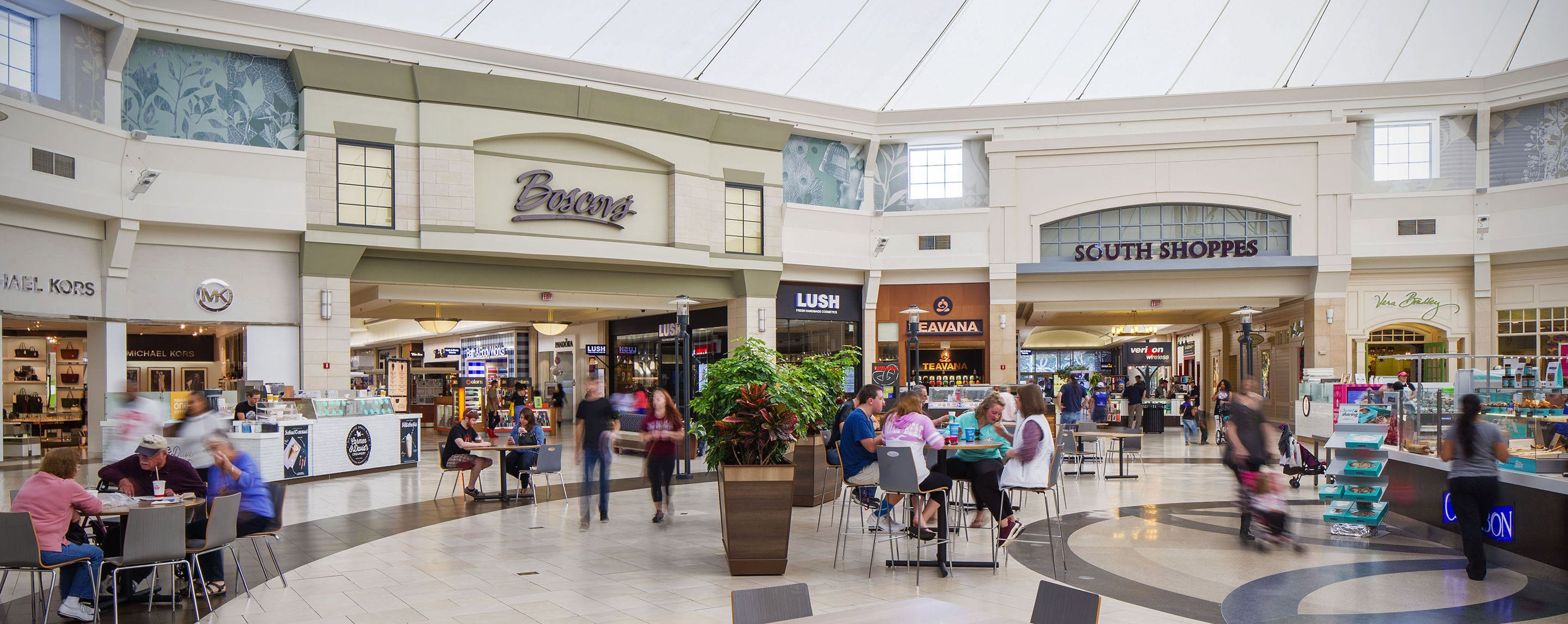 People walk around and sit in an open area of a shopping mall with stores like Lush, Pandora, Verizon and Michael Kors nearby