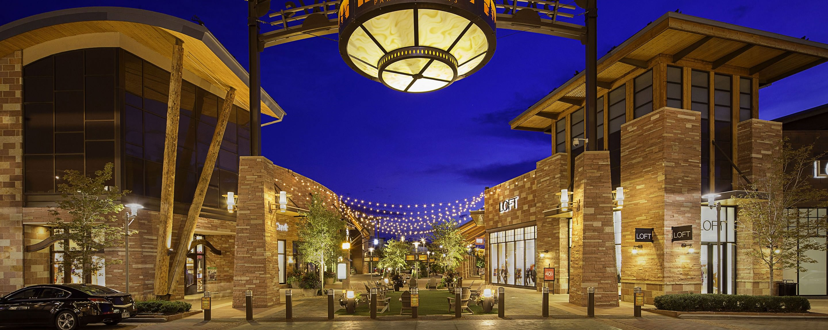 A large light fixture hangs over the entrance to a mall courtyard containing a LOFT store, among others.