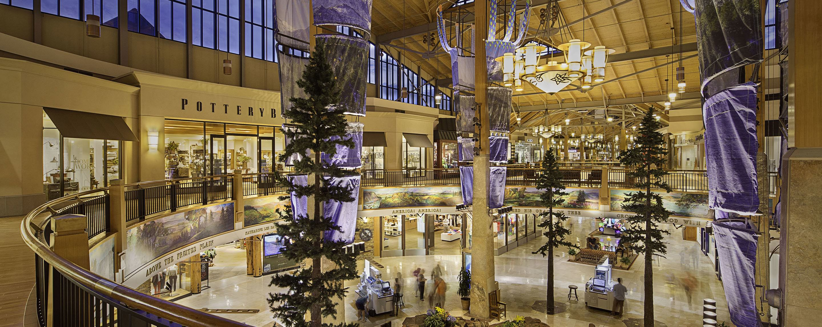 A pine tree display set up inside a mall with a large chandelier and a Pottery Barn on the second floor.