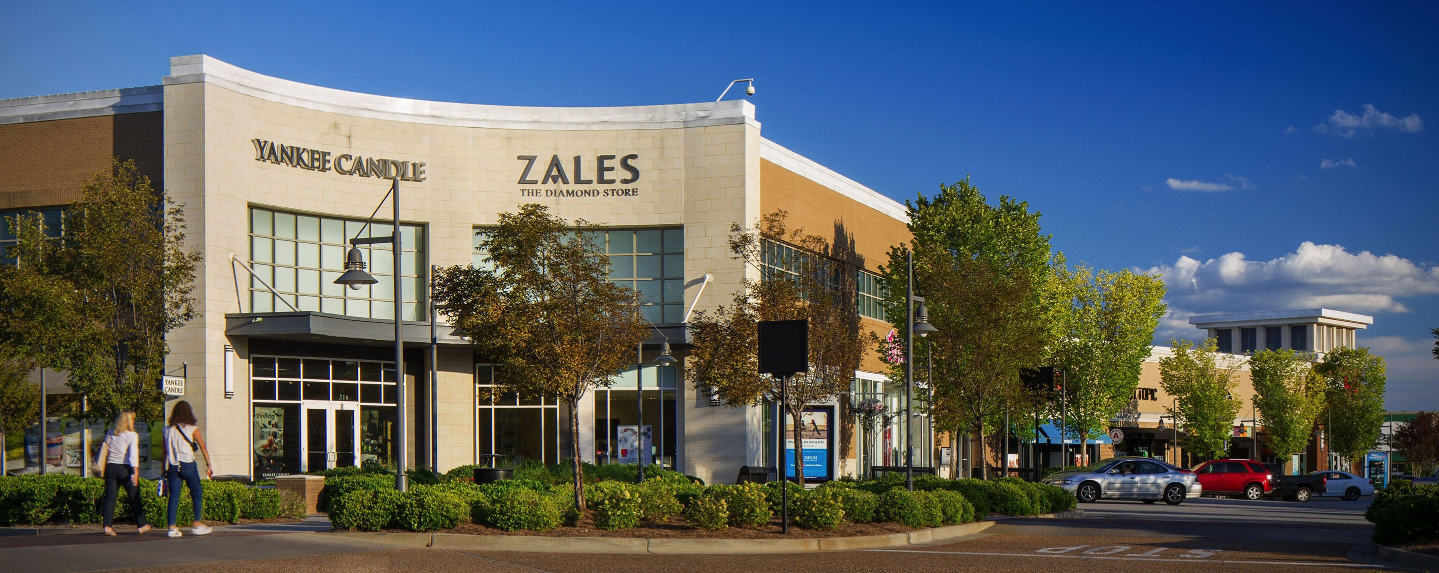 A Zales and Yankee Candle store are seen at an outdoor shopping center. Cars are parked on the side of the buildings.