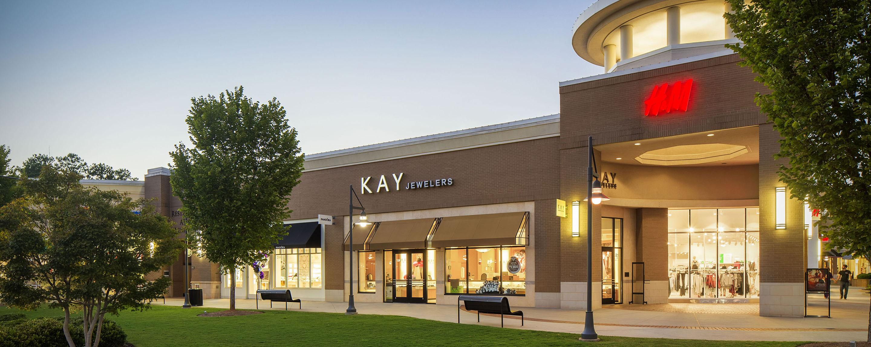 Benches sit on the sidewalk outside of a shopping center with businesses such as Kay Jewelers and H. M.