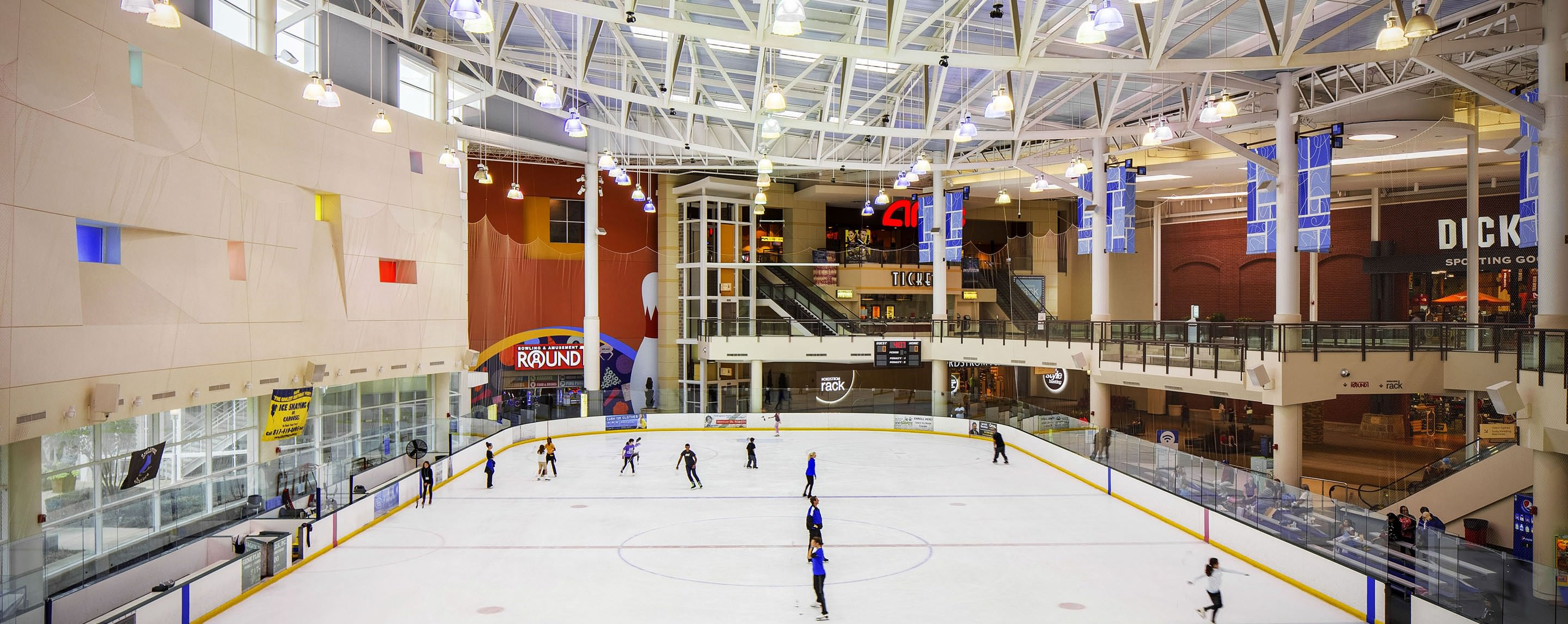 An image of an indoor skating rink at a mall. Dick's Sporting Goods is visible in the background.