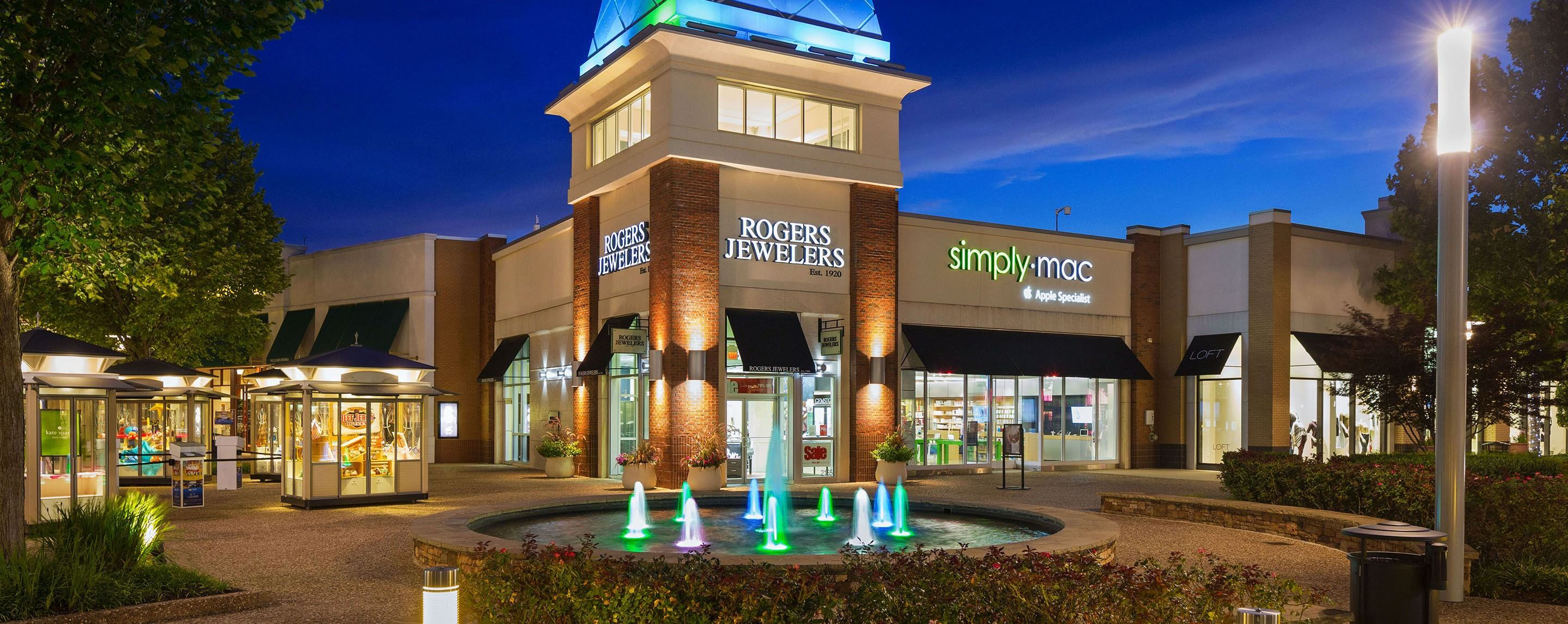 A colorfully lit fountain stands in front of Pinnacle Hills mall. Rogers Jewelers can be seen in the background.