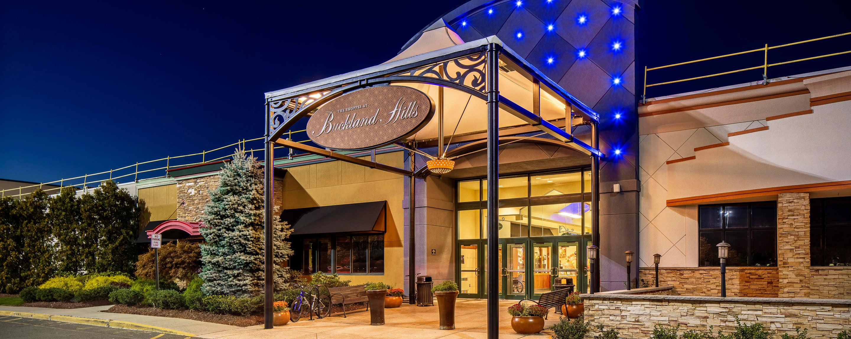 A sign with blue lighting illuminated the building near the Shoppes at Buckland Hills at nightfall.