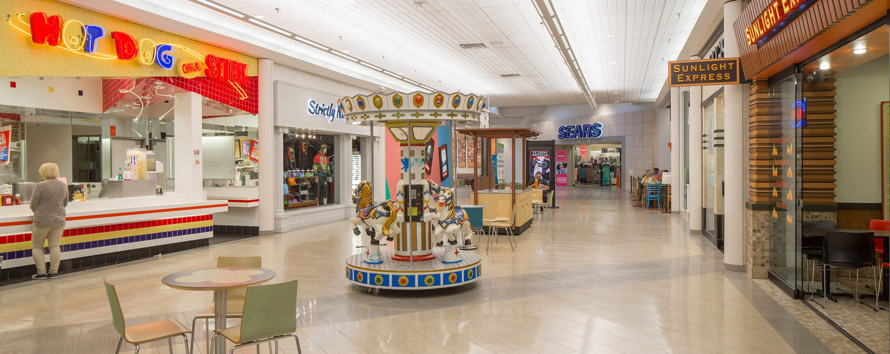 A children's ride can be seen the hallway of an indoor mall. A Sears storefront stands in the backgroudn.