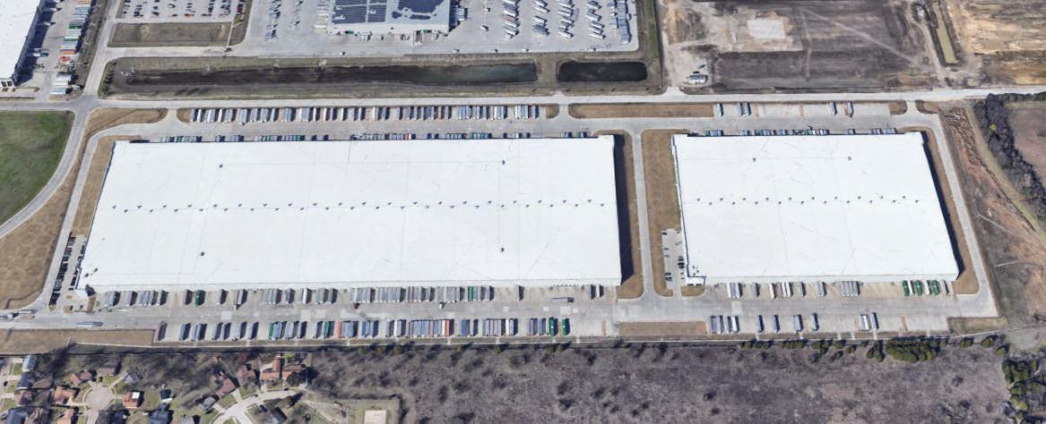 Top view of a few large buildings with white roofs that is surrounded by cars parked in the lot.