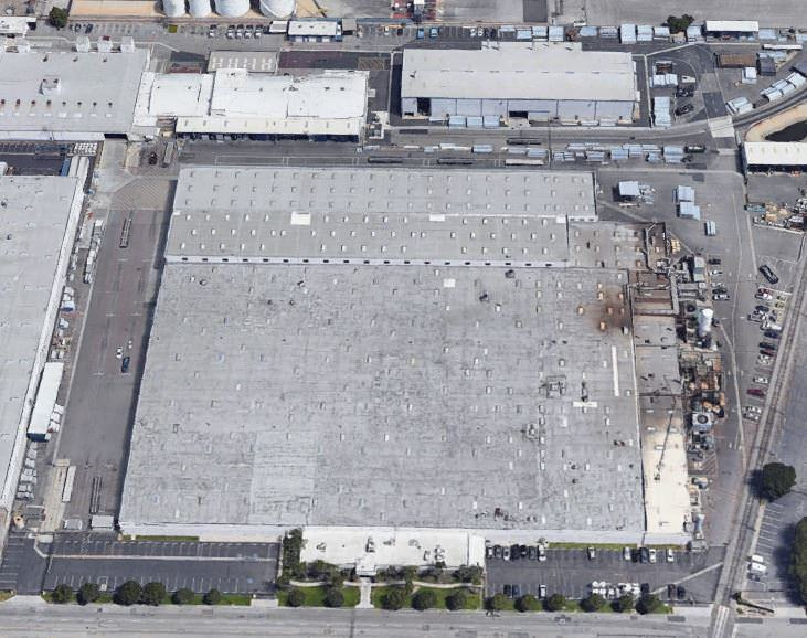 An outdoor and upper view of a large squared parking lot to park vehicles and some building around t