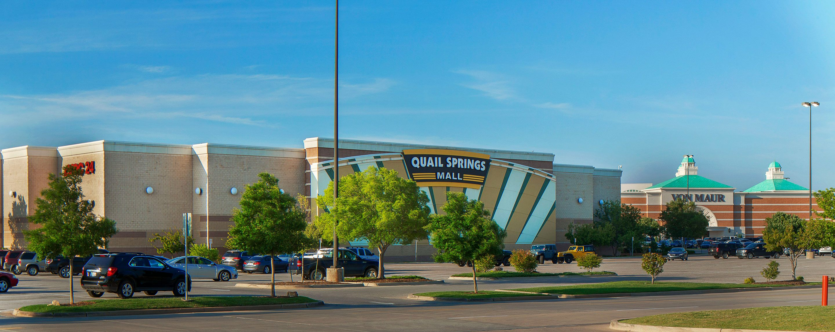 An outside shot of Quail Springs Mall in daytime. A sign for AMC is on the side of the building.