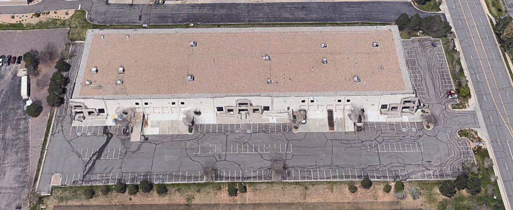 Top view of a white building with a brown roof that is next to cars parked in the lot.