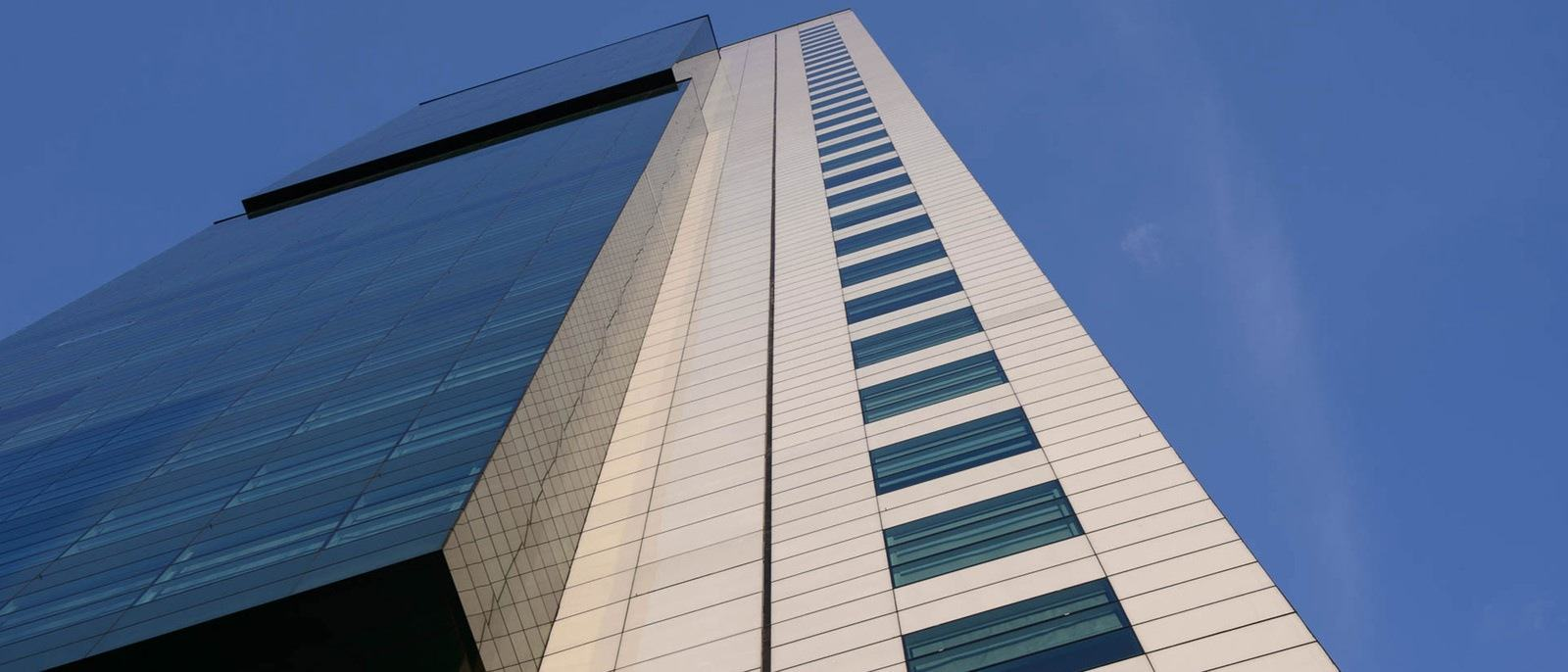 A tall building with brown walls and tinted windows pointing towards the blue sky.