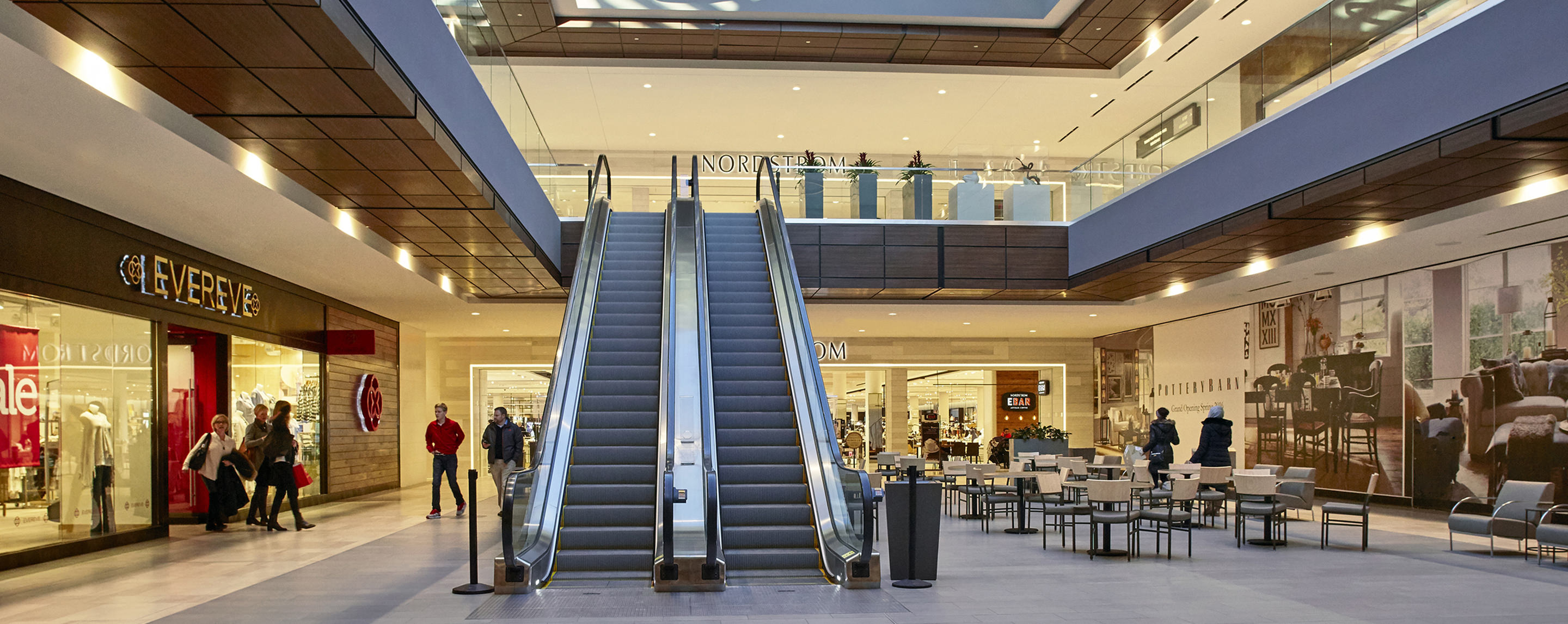 Escalators leading to the second floor of a mall are near an unoccupied seating area, Evereve and a Nordstrom store and Ebar.