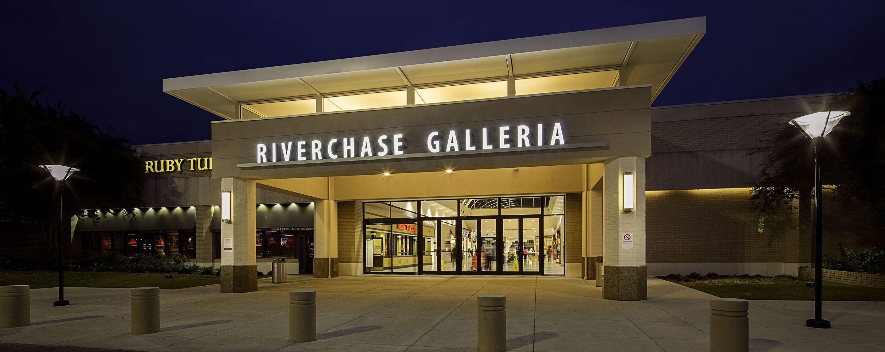 """The sign saying """"Riverchase Galleria"""" is lit up at night. Near the entrance to the building is a Rub"""