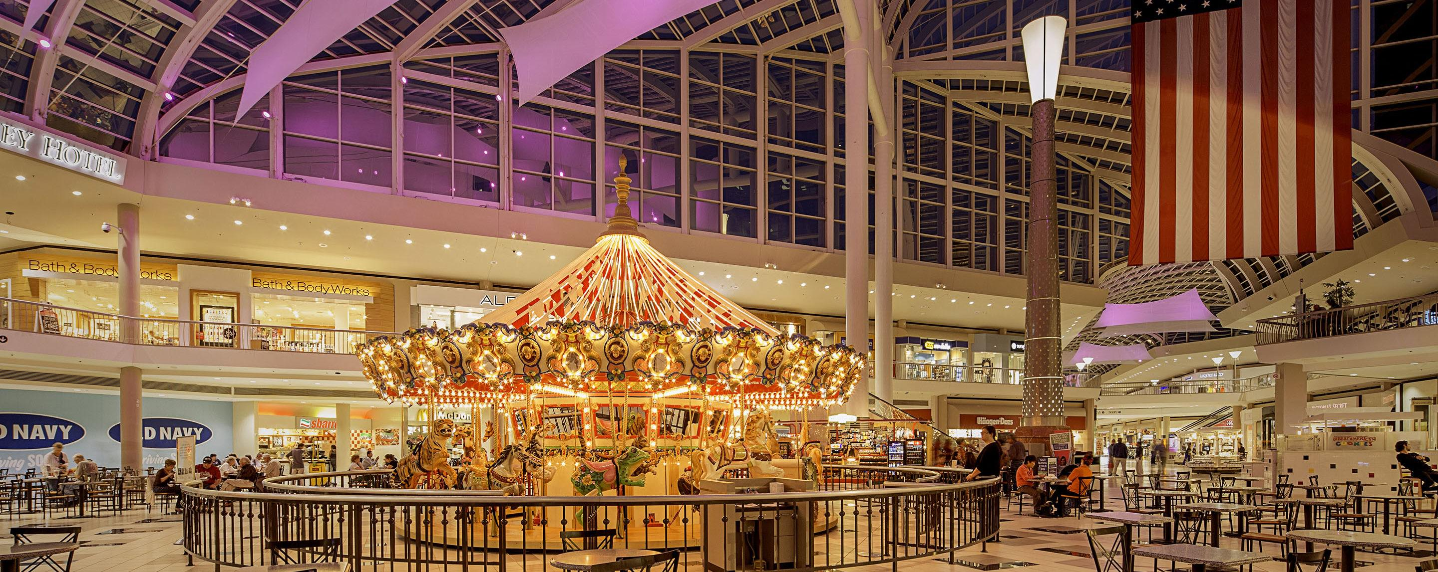 A shot of tables and a well lit carousel in the middle of a glass-roofed mall at night.