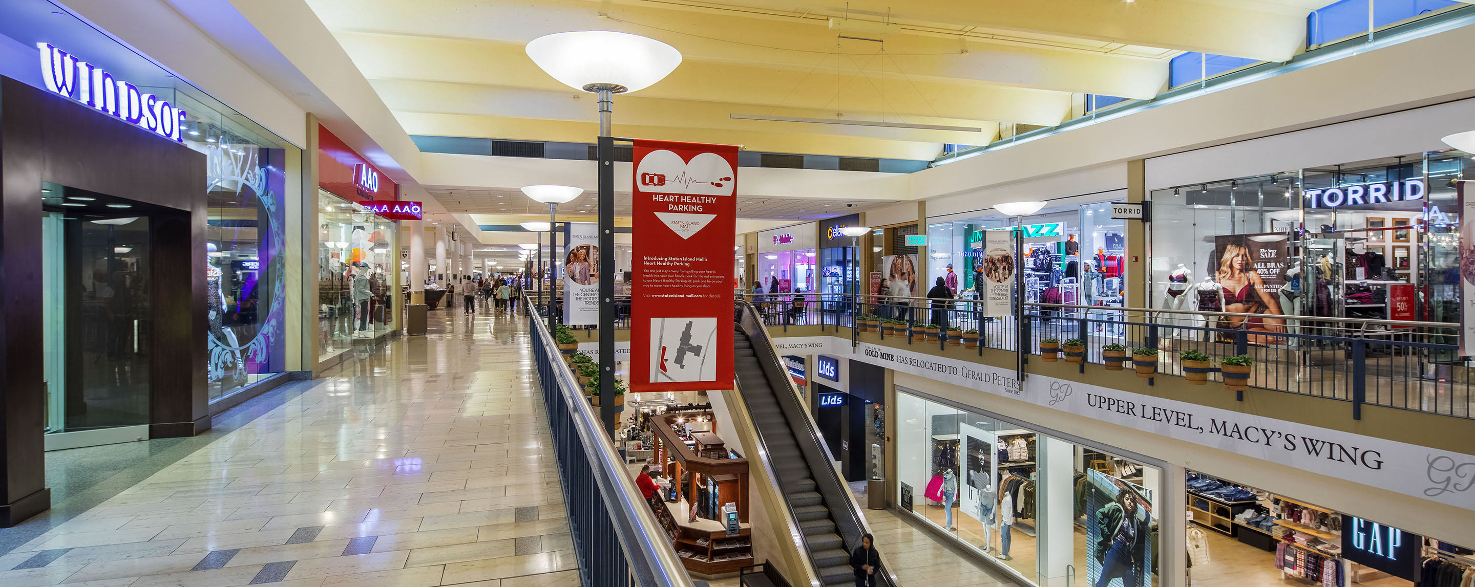 An indoor multilevel mall with an escalator featuring stores by GAP, Lids, and TORRID.