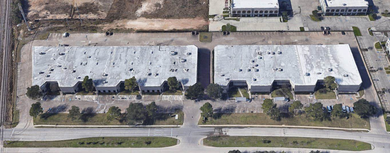 An aerial view of two buildings that look like warehouses or office spaces.