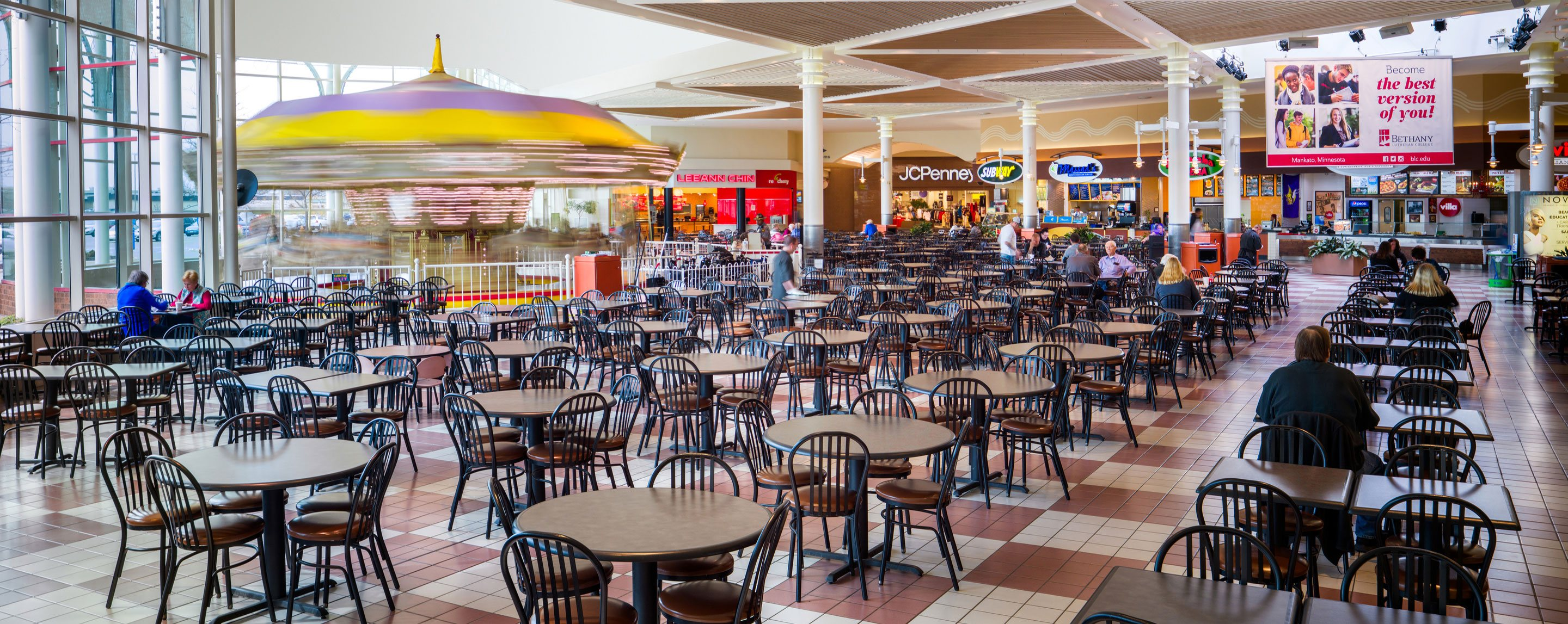 A mostly empty dining area at a food court with numerous tables with basic chairs. JCPenney and Subway are nearby.