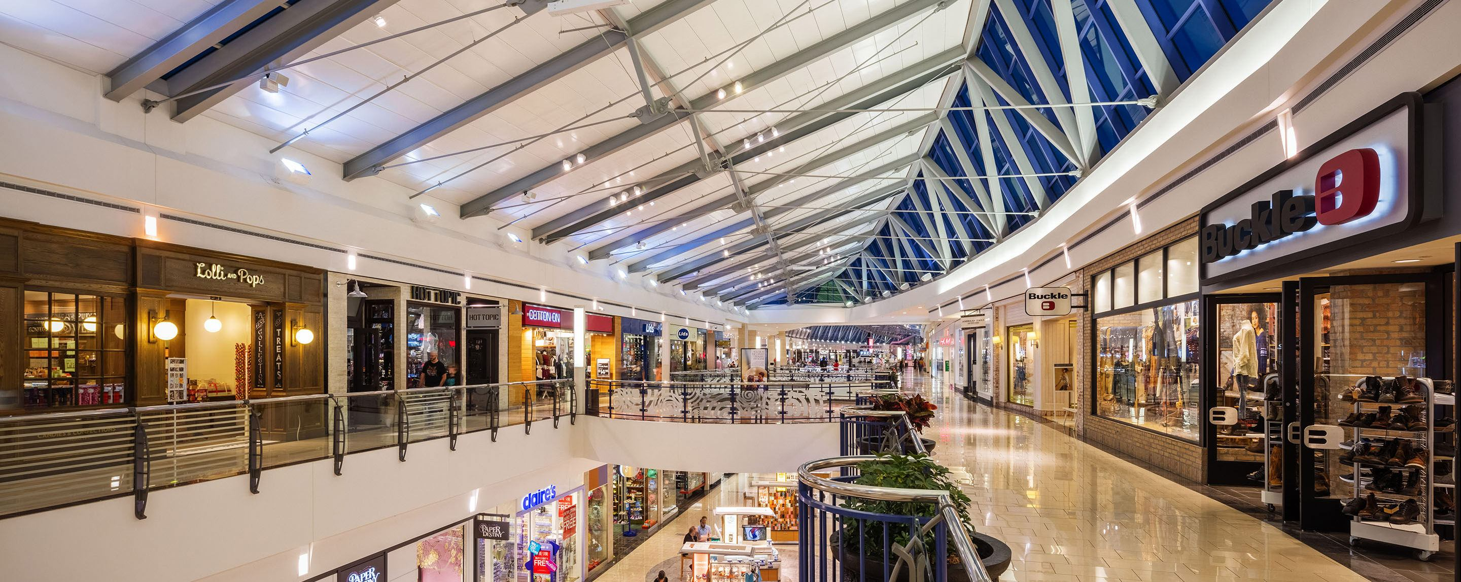 Lids, Cotton On, Claire's, Hot Topic, and Buckle stores are inside a two-story indoor shopping center with upper skylights.