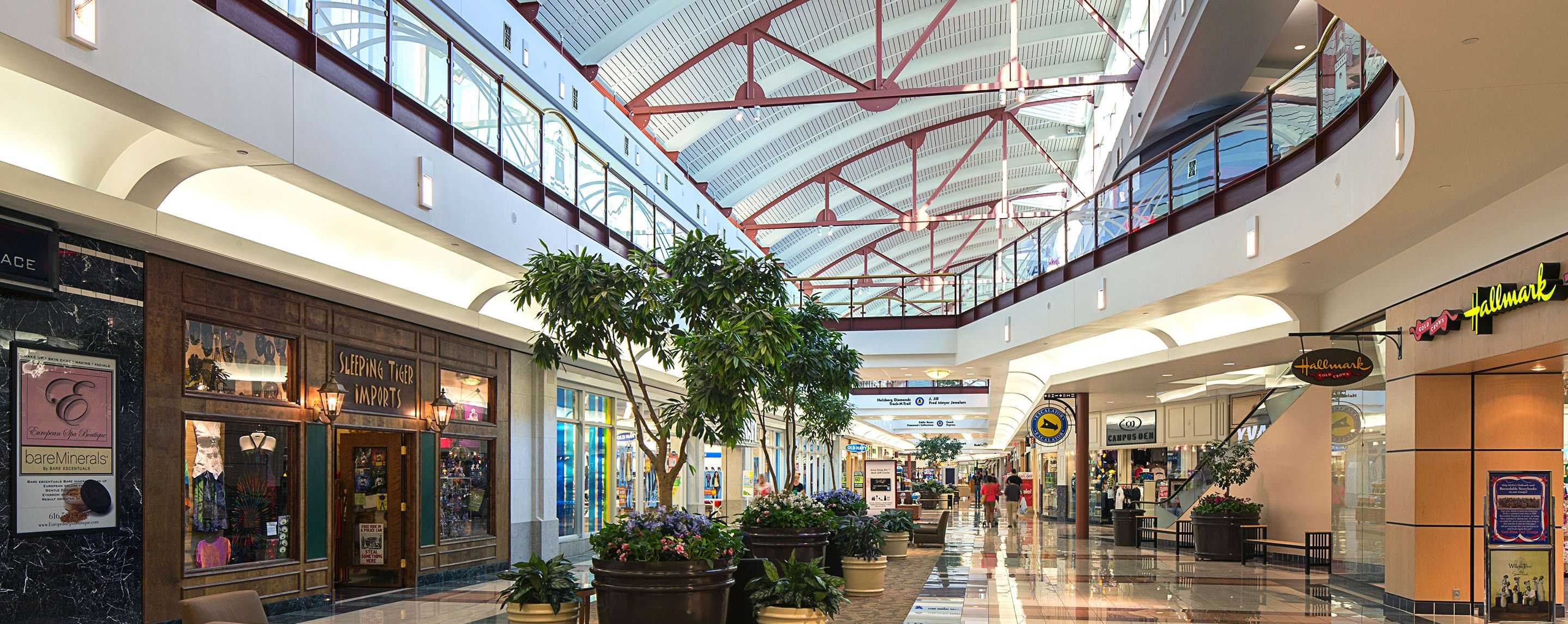 An empty indoor mall with an open ceiling and potted plants. Hallmark, Sleeping Tiger, and Old Navy locations are present.