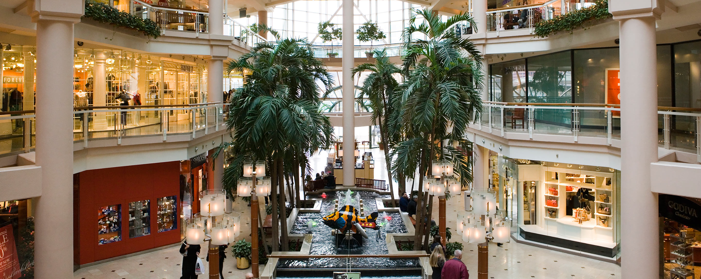 The atrium of a multi-story mall. An indoor fountain is lined with rows of palm trees.