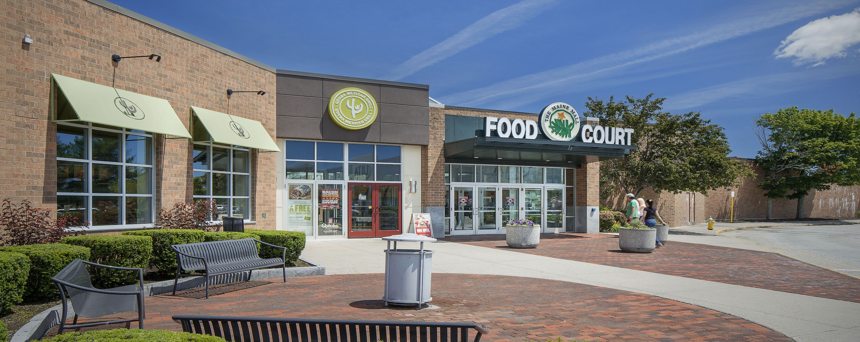 "An exterior shot of a mall in daylight. A large sign above a set of doors reads ""Food Court"""
