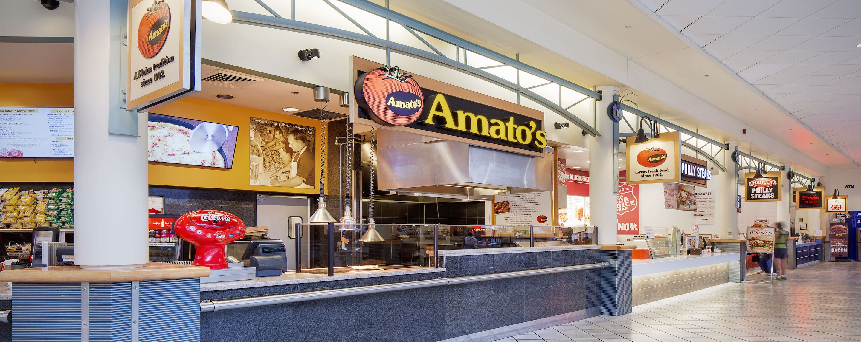 Arby's, Amato's, and Charlie's Philly Steaks stand side by side in an empty food court in a shopping center.