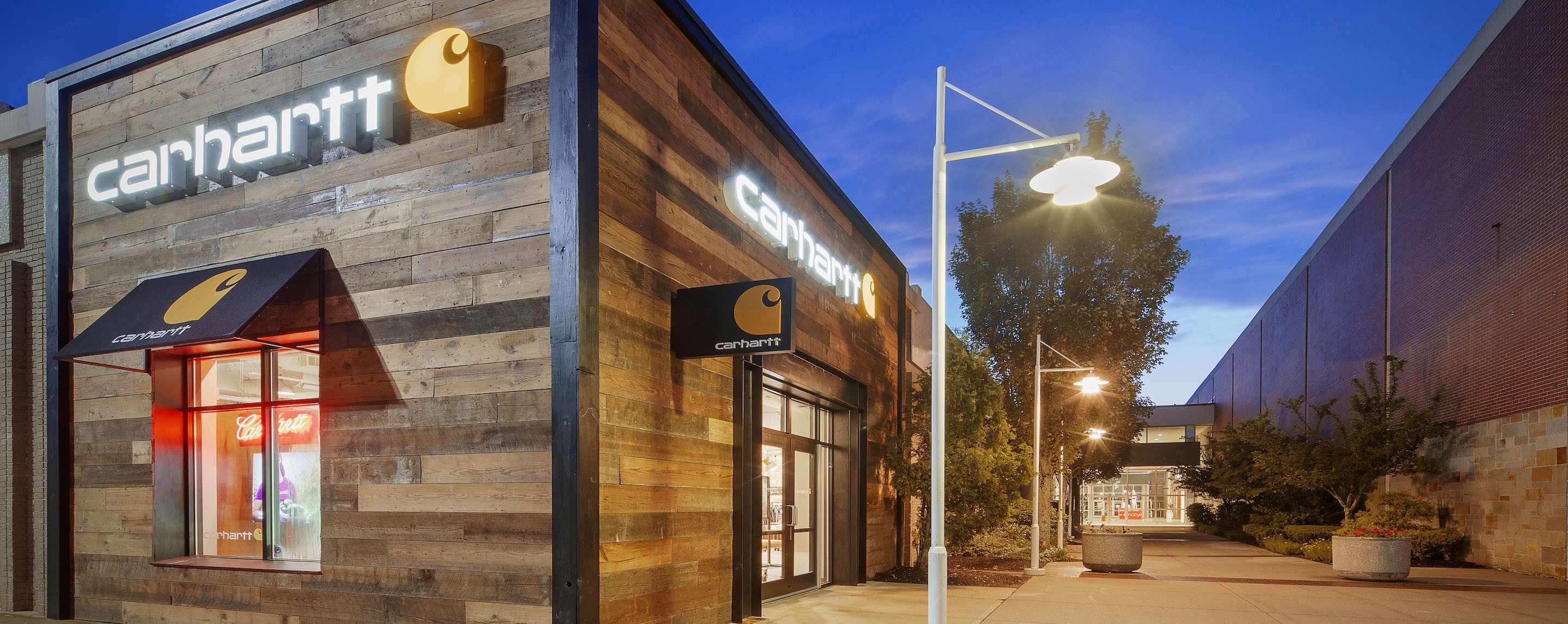 A light stands in the alley of a Carhartt store with trees in the alley.