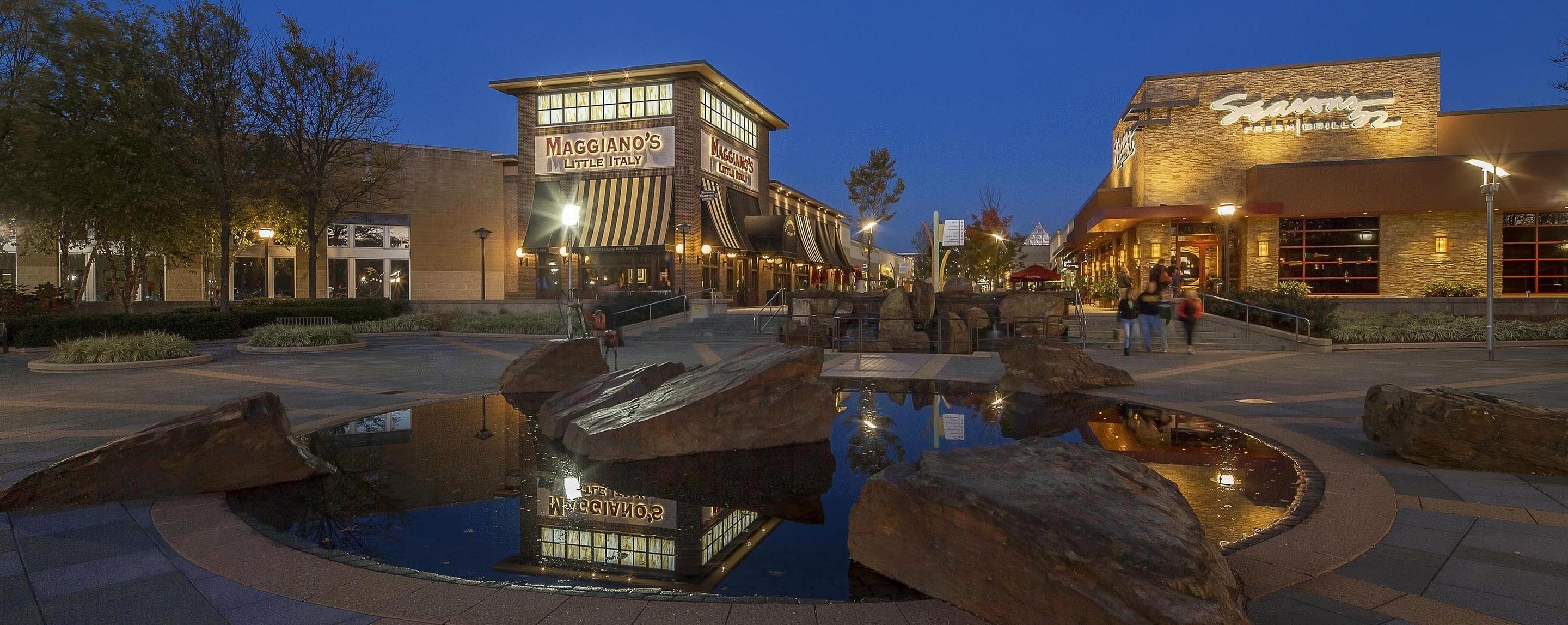 A manmade pond sits in the cement area in front of a shopping center outside.