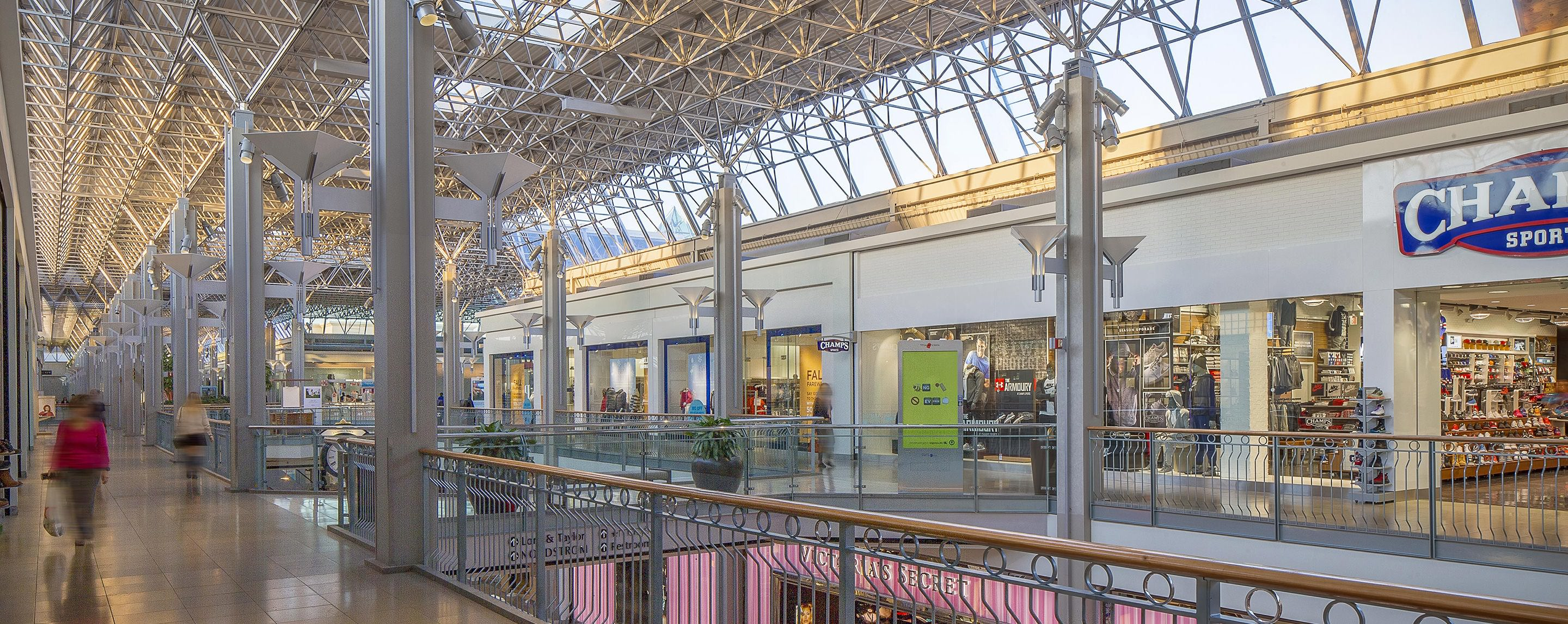 People walk on the second floor of an indoor shopping center and pass by stores such as Champs.