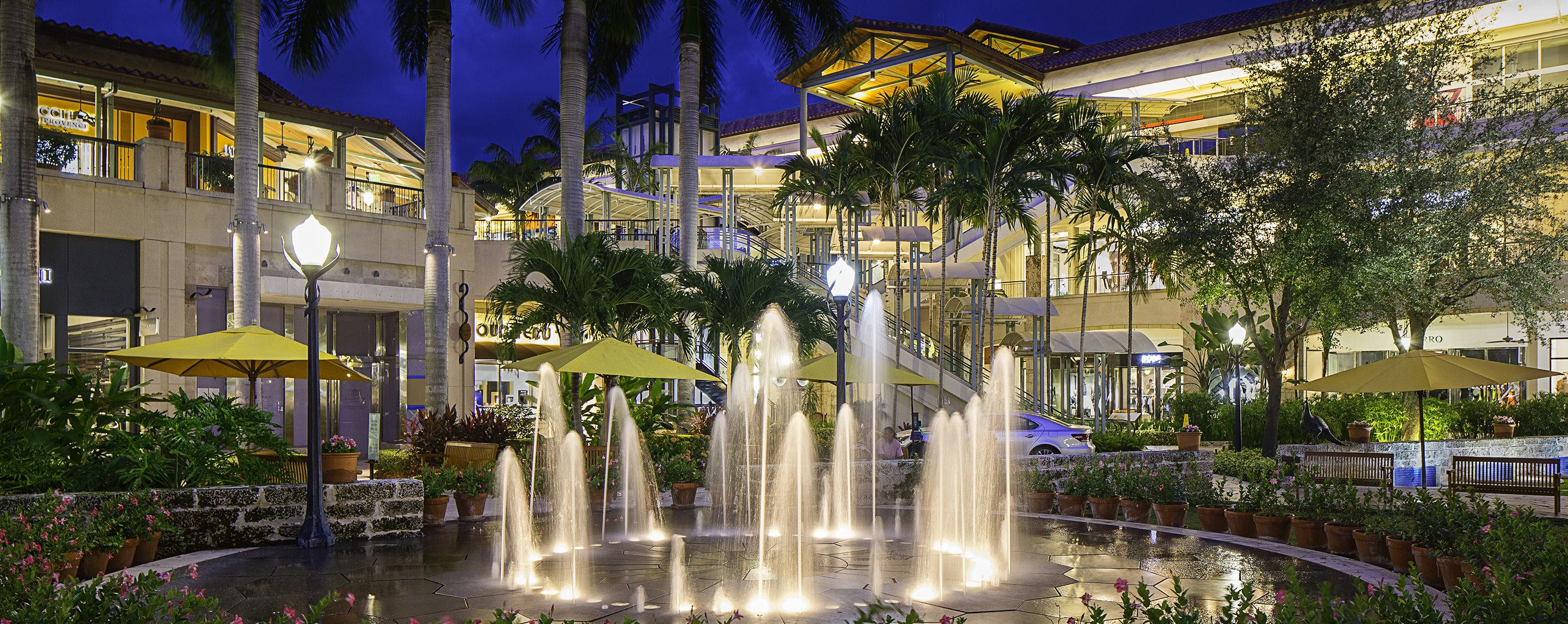 A fountain illuminated by lampposts in front of a shopping center. There are yellow umbrellas behind