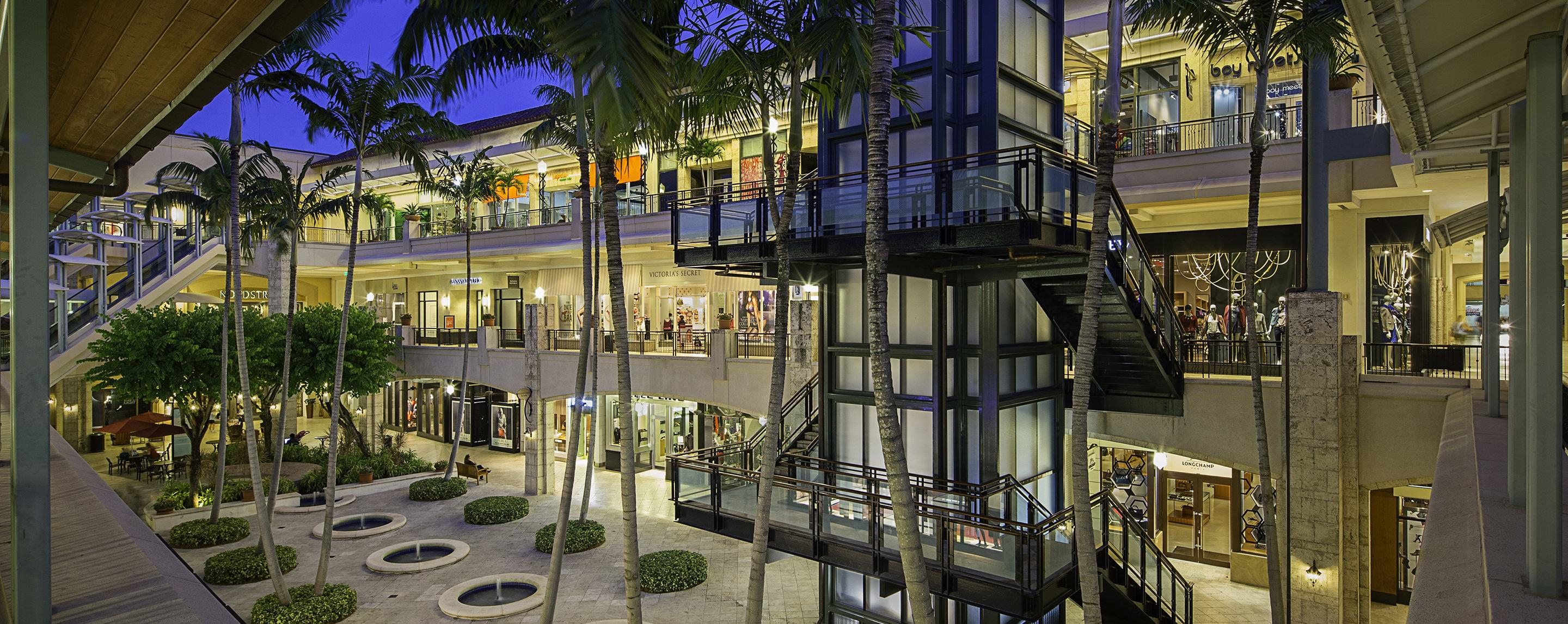An outdoor enclosed shopping center with palm trees planted in the middle and three stories of shops.