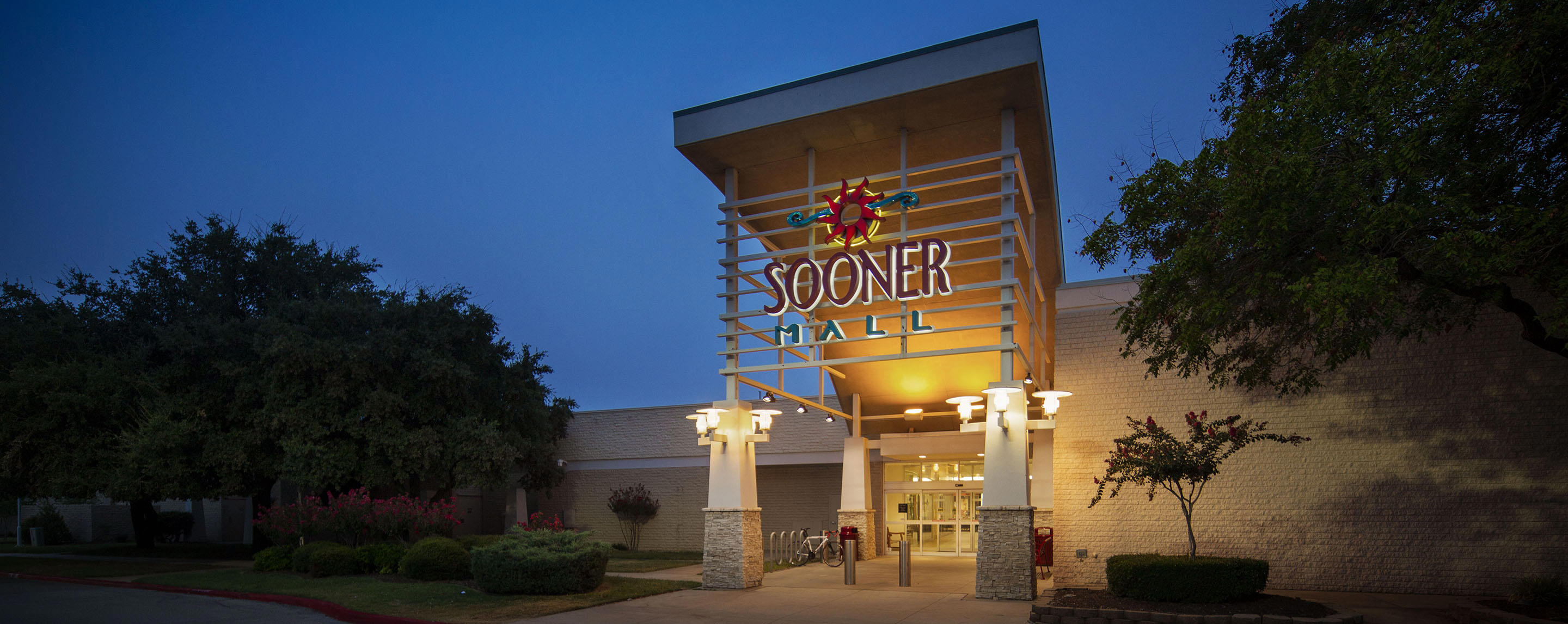 A sign on the outdoor entrance to Sooner Mall is lit up and surrounded by trees.