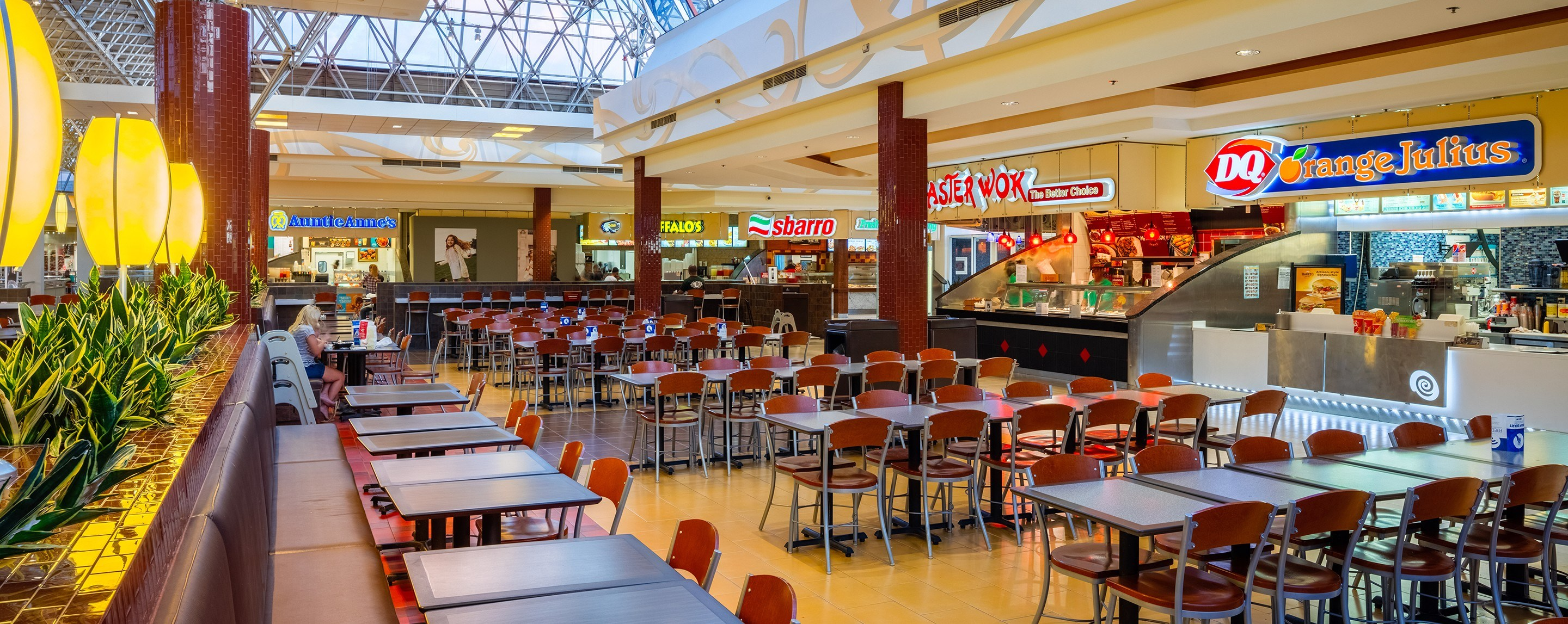 Empty tables and chairs in a food court featuring Sbarro. There are skylights and planters behind the booths.