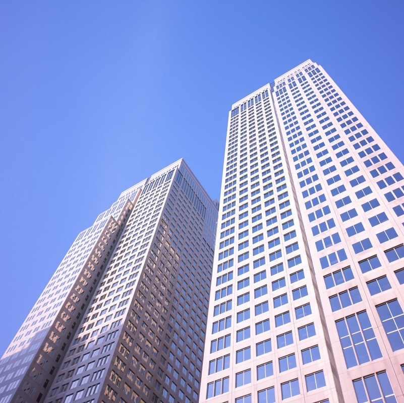 View looking up at two tall white skyscrapers from below.