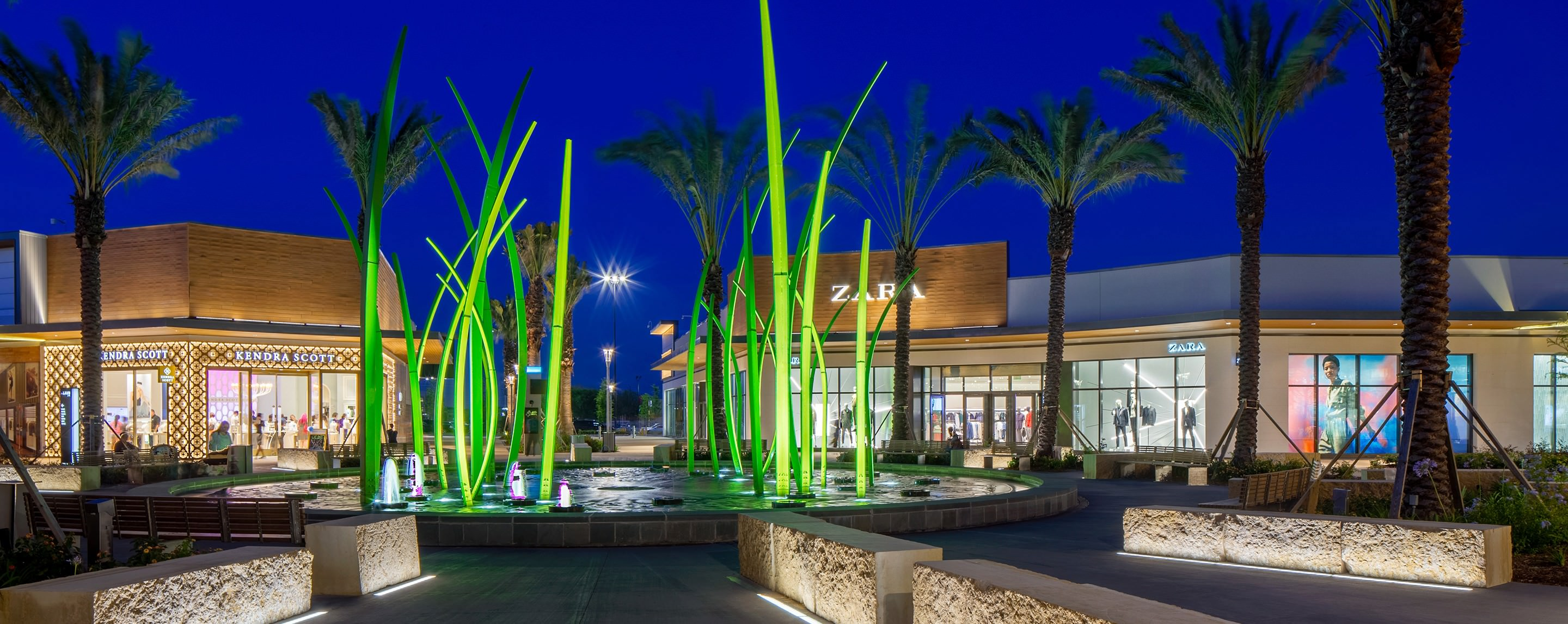 The outside of a mall is decorated with palm trees, a fountain and various fake plants.  There is a Zaras in the background.
