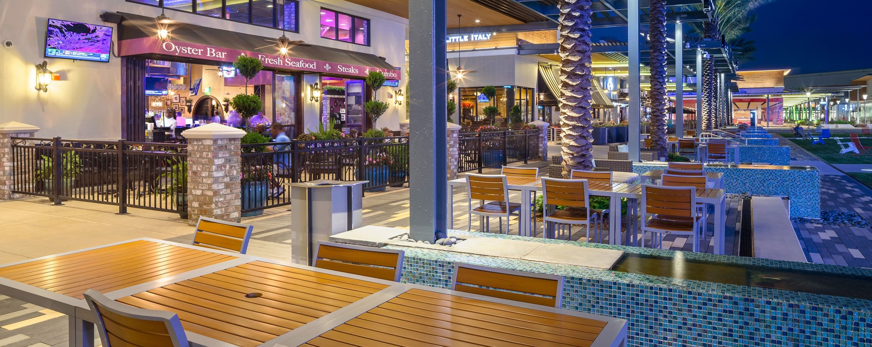 Sets of tables sit unoccupied outside of a restaurant in a shopping center.