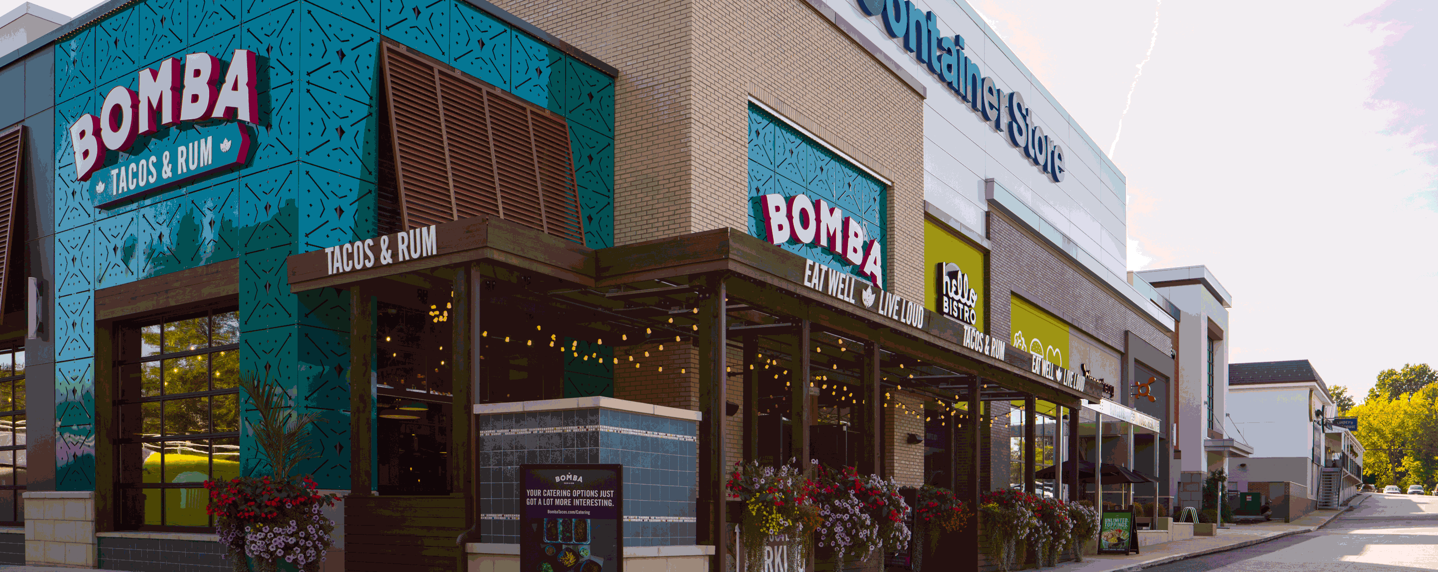 Exterior shot of storefronts including Bomba, Hello Bistro, and the Container Store.