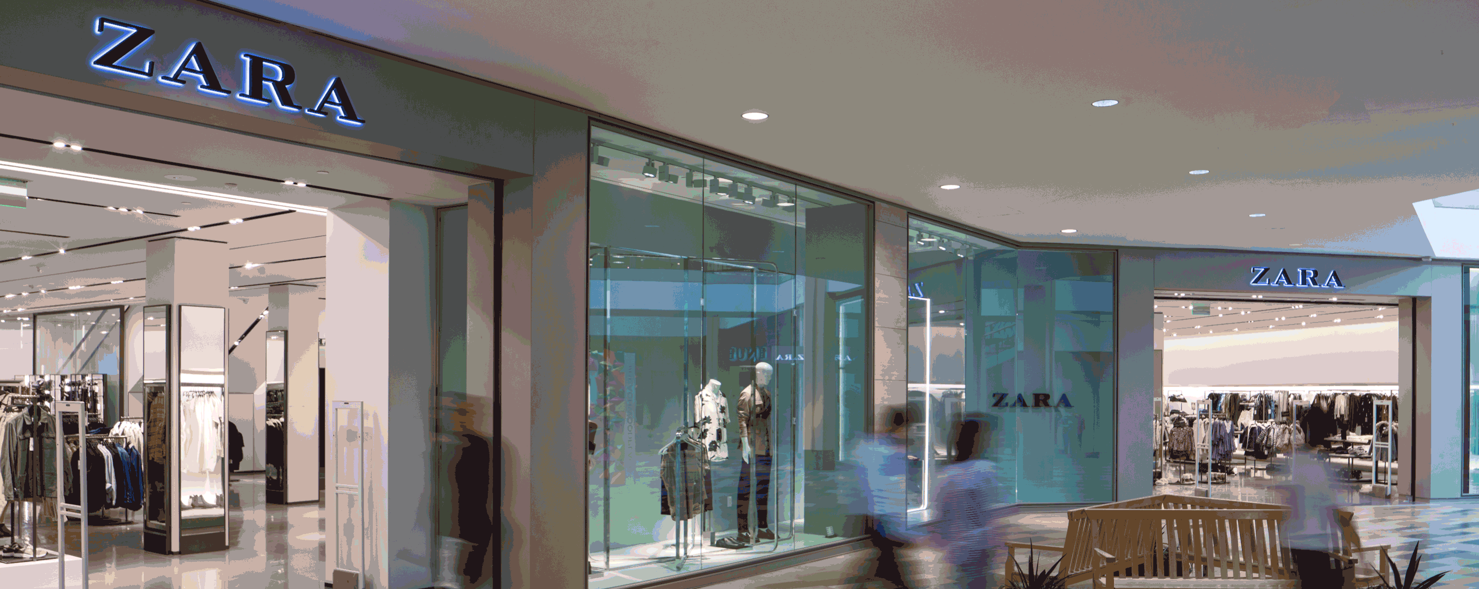 A picture of the Zara storefront with people moving in the foreground.