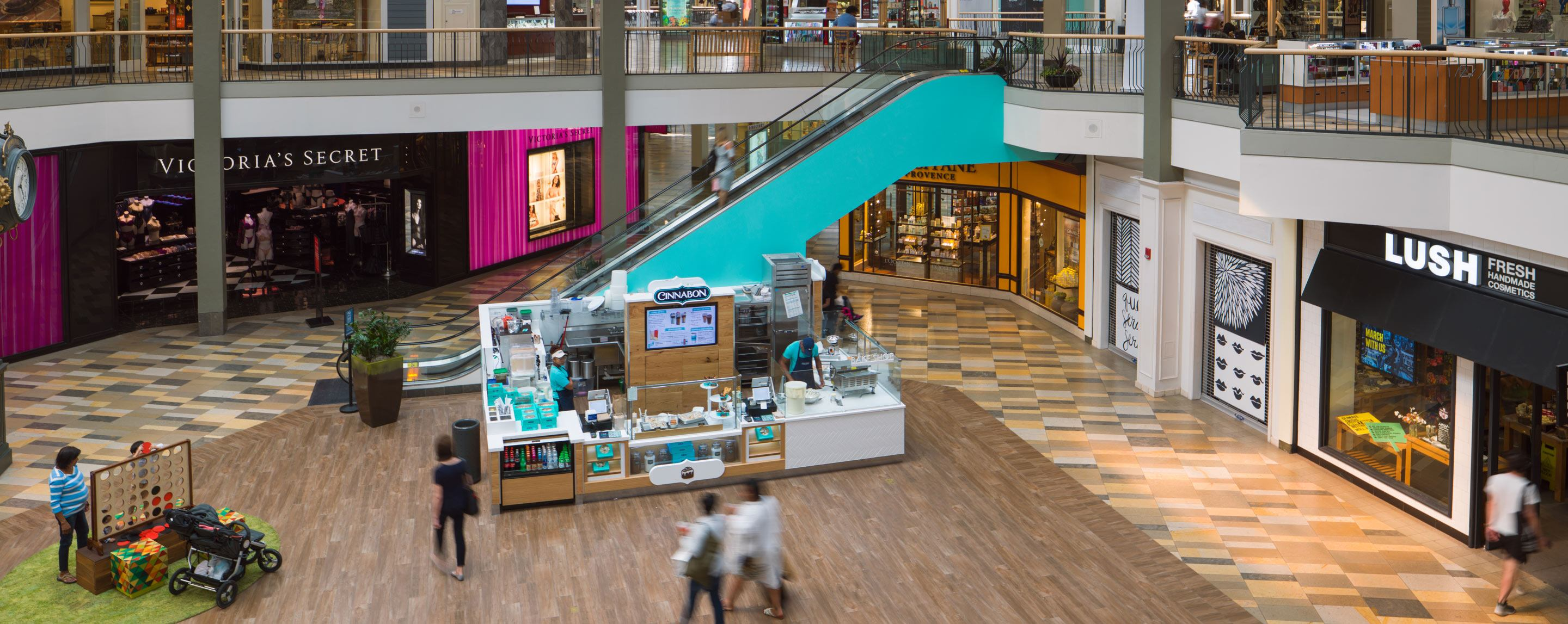 A blue escalator leads to the second floor of a mall. Stores such as Lush and Cinnabon are visible.