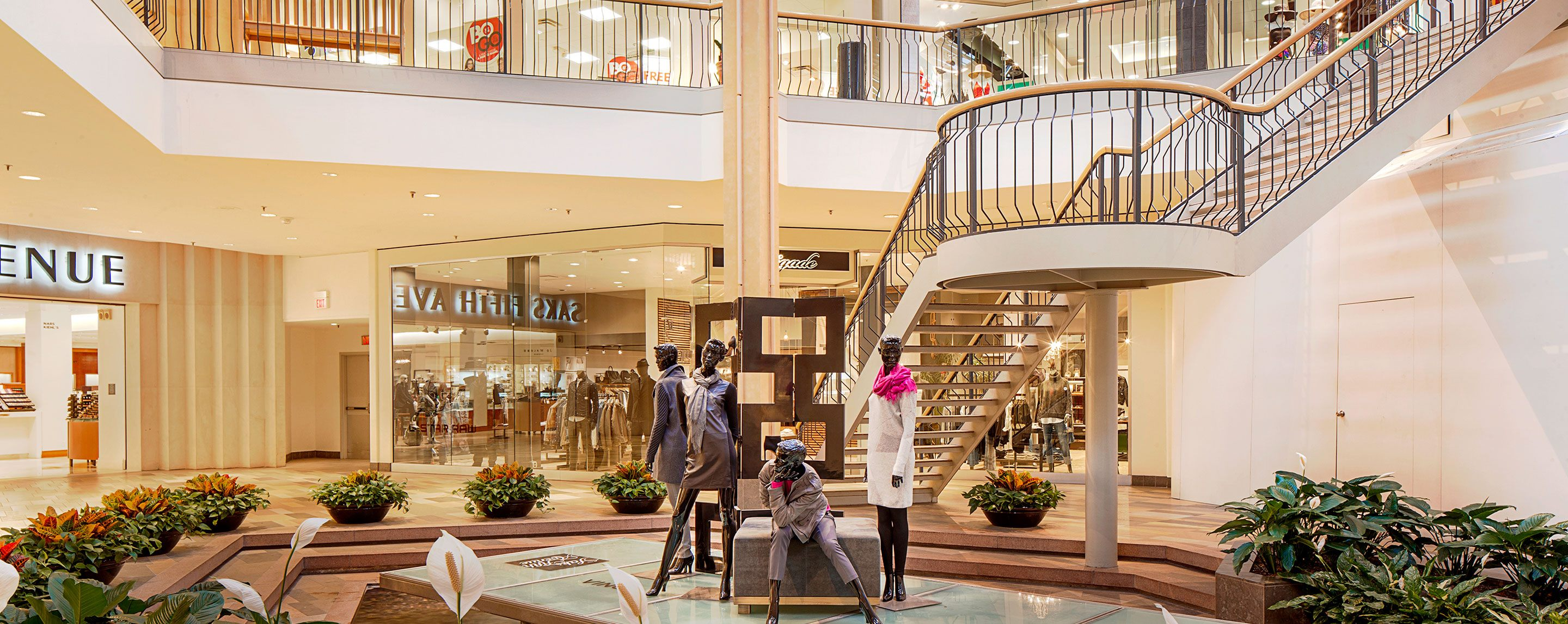 A display of clothed bronze mannequins stands in the mall's plaza near Saks Fifth Avenue.