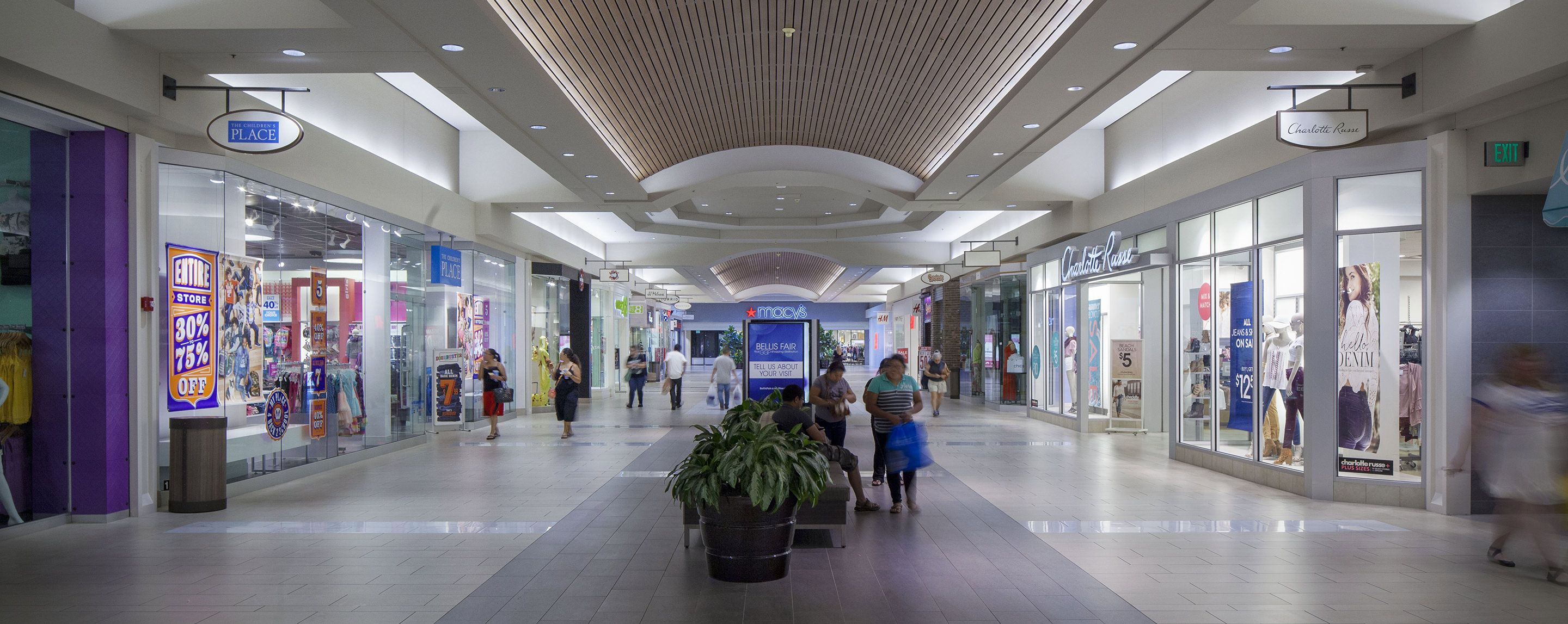 People walk down the corridor of a shopping center and pass by stores like Torrid and Charlotte Russe.