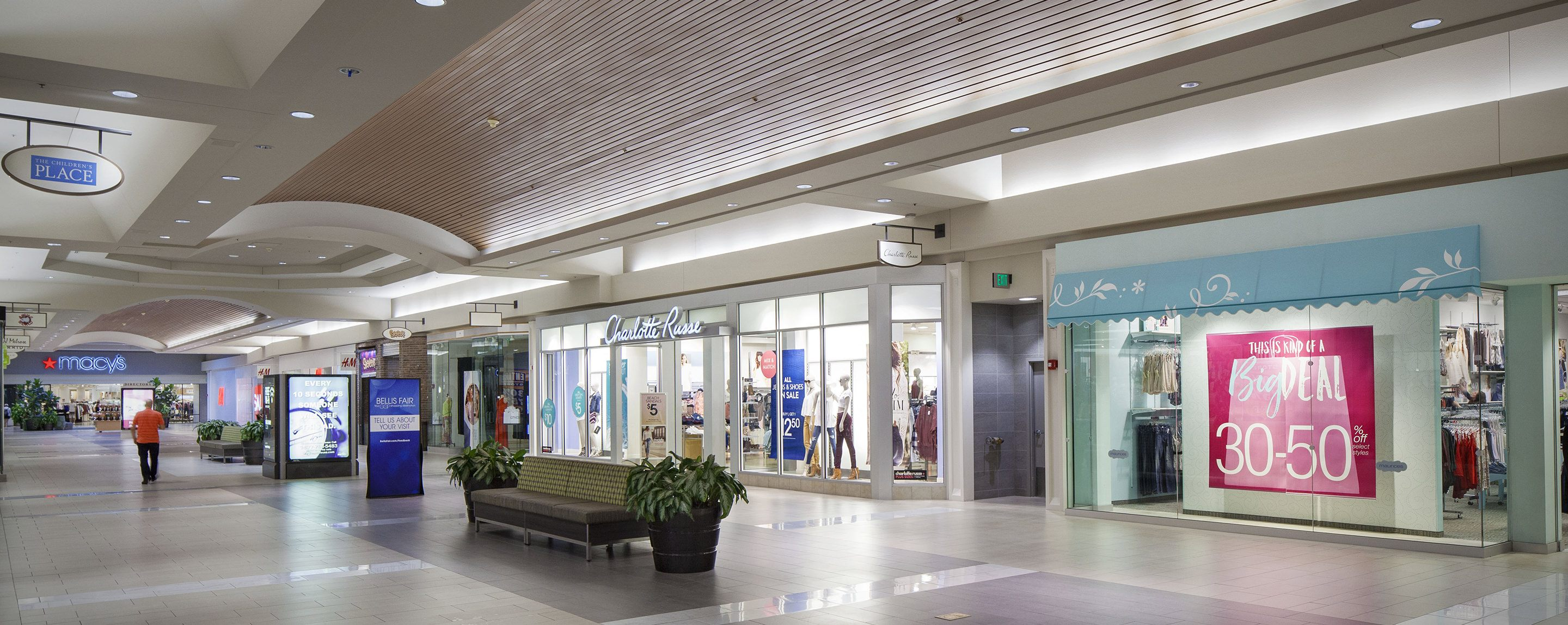 Stores such as Charlotte Russe and H.M.  can be seen in a hall of an indoor mall with a Macy's store at the end.