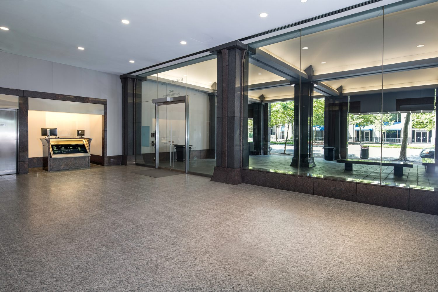A lobby with dark gray tile and large glass windows.