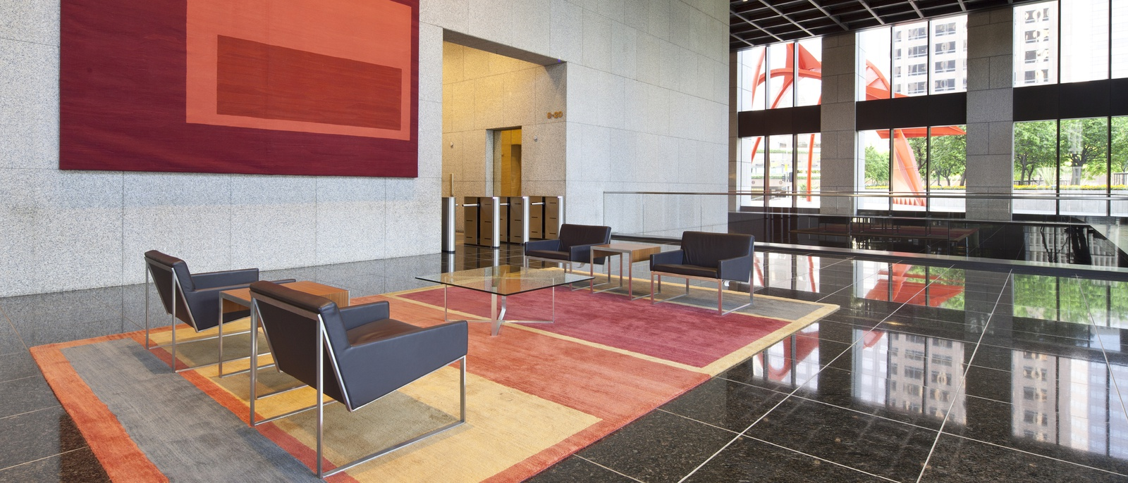 Lobby with tiled black floor, large windows, and seating area,