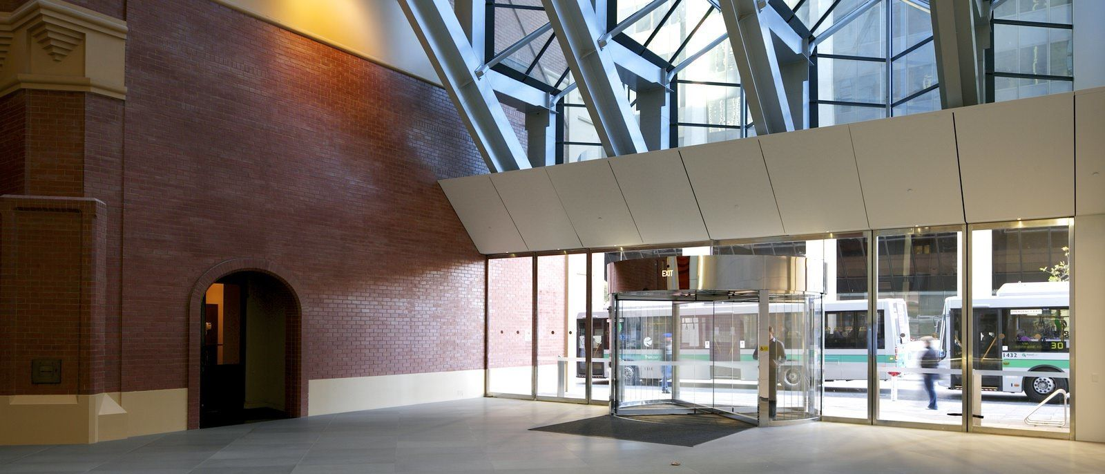 Indoor lobby of a large building with walls that are lined with bricks and huge panels of glass.