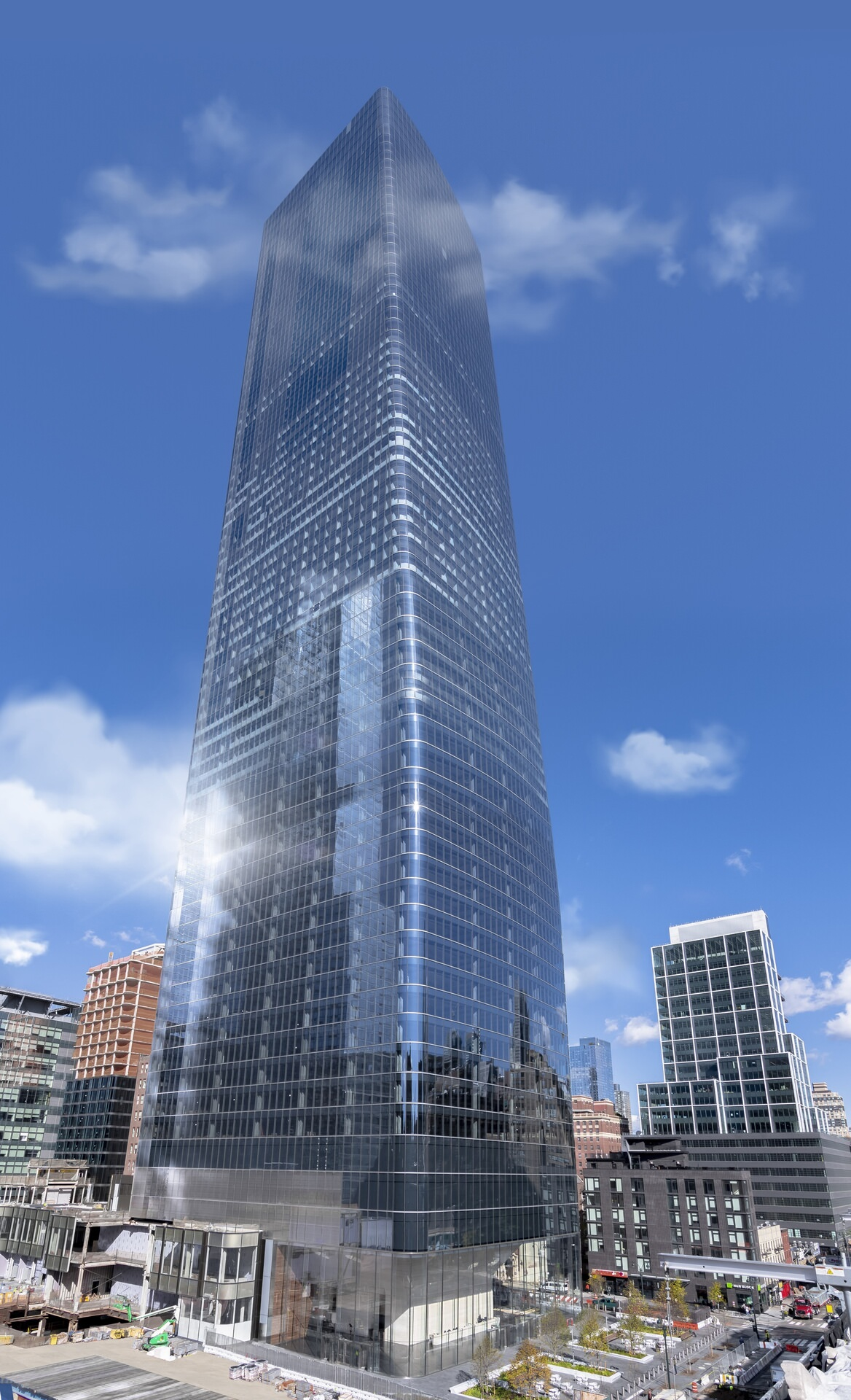A very large skyscraper that is located in a downtown area and is made with a lot of glass.